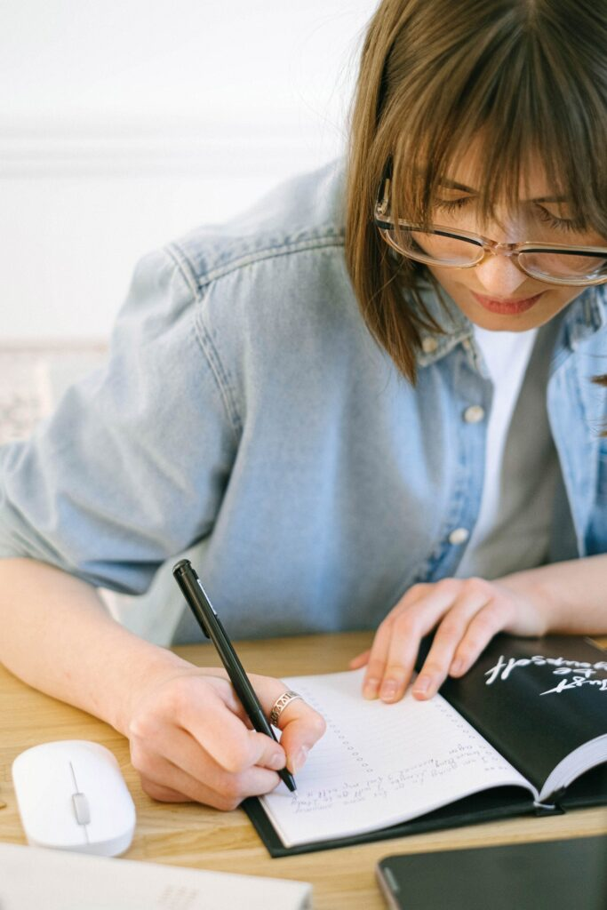 A woman wearing glasses writes in a journal.